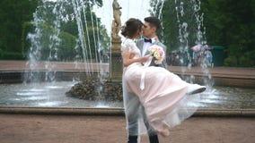 O noivo guarda a noiva em seus braços e beijos no fundo da fonte vídeos de arquivo