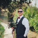 O noivo guarda o ramalhete e as poses para a câmera imagens de stock