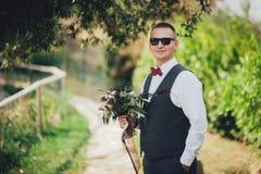 O noivo guarda o ramalhete e as poses para a câmera imagens de stock royalty free