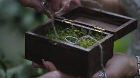 O noivo guarda uma caixa de presente da joia com alianças de casamento do ouro a mão do ` s do homem toma a aliança de casamento  Fotos de Stock