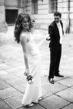 O noivo guarda uma fita no vestido da noiva quando rir imagens de stock