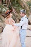 O noivo guarda o vestido da noiva na garganta no fundo das montanhas fotos de stock