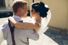 O noivo leva a noiva em seus braços foto de stock