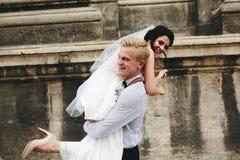 O noivo leva a noiva em seus braços foto de stock royalty free