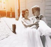 O noivo leva a noiva em seus braços Imagens de Stock Royalty Free