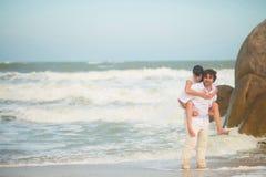 O noivo leva a noiva em sua parte traseira contra o mar e as rochas fotografia de stock