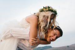 O noivo leva a noiva no seu parte traseira fora Imagem de Stock