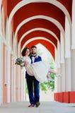 O noivo leva sua noiva em seus braços fotografia de stock royalty free
