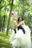 O noivo leva sua noiva na parte traseira no parque foto de stock royalty free