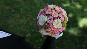 O noivo levanta acima um ramalhete do casamento em sua mão Ramalhete bonito do casamento de flores frescas filme