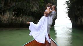 O noivo levanta a noiva pela cintura que está no barco de madeira do longtail filme