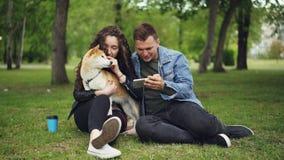 O noivo loving está mostrando que tela do smartphone à jovem senhora bonita que é guardando e patting a bem-produziu o cão quando video estoque