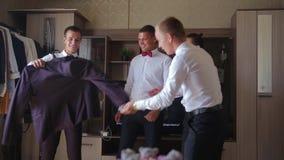 O noivo mostra o revestimento a seus amigos que apreciaram sua escolha, a seguir revestimento dos lances do noivo em seus ombro e filme