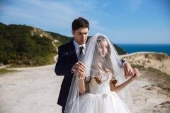 O noivo no terno vem à noiva de trás e quer tirar o véu de sua cara foto de stock