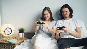 O noivo novo bonito e a amiga dos pares estão jogando o videogame na cama em casa video estoque