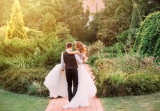 O noivo novo em um terno leva nos braços sua noiva, vestindo um vestido branco luxuoso magnífico longo, andando na surpresa foto de stock royalty free