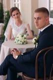 O noivo olha a câmera ao sentar-se em uma tabela Imagem de Stock Royalty Free