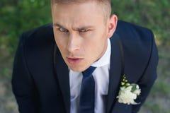 O noivo olhando de sobrancelhas franzidas olha na câmera com sua cabeça Imagens de Stock Royalty Free
