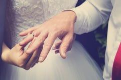 O noivo põe o anel sobre o dedo da noiva, close-up das mãos Tonificação ao estilo do instagram imagens de stock
