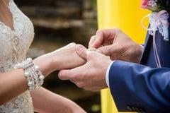 O noivo põe sobre o anel do ` s da noiva imagens de stock royalty free