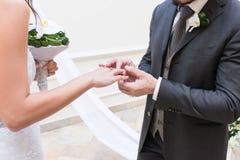 O noivo põe sobre um anel sobre o dedo do ` s da noiva imagens de stock royalty free