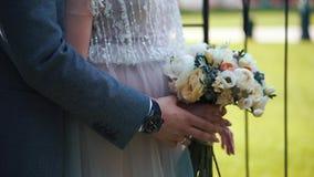 O noivo põe suas mãos sobre o abdômen da noiva A noiva guarda flores em suas mãos Mãos do close-up somente filme