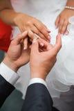 O noivo põr o anel sobre seu dedo da noiva Imagem de Stock