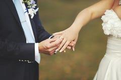 O noivo pôs uma aliança de casamento sobre o dedo de sua noiva bonita Fotografia de Stock
