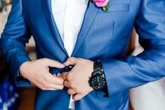 O noivo prende o botão no revestimento fotografia de stock