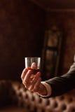 O noivo realiza em sua mão um o vidro do uísque fotos de stock