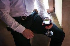 O noivo realiza em sua mão um o vidro do vinho tinto imagens de stock