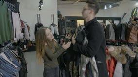 O noivo recusa guardar a roupa para que sua amiga tente sobre em uma alameda da loja de disconto quando a compra louca - vídeos de arquivo