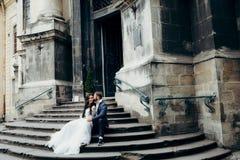 O noivo triguenho considerável está beijando levemente a noiva atrativa na cabeça ao sentar-se nas escadas do barroco velho Fotografia de Stock Royalty Free