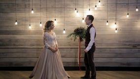 O noivo vem à noiva feliz, abraçando para trás a casa de madeira interna filme