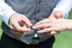 O noivo veste o anel do ` s da noiva imagens de stock