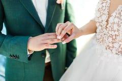 O noivo veste o anel no dedo do ` s da noiva Dia do casamento imagens de stock