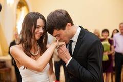 O noivo veste o anel em seu dedo no escritório de registro Foto de Stock