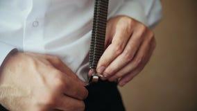O noivo veste os suspensórios - traje do casamento para o homem filme