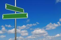 O nome verde em branco da rua assina Agains um azul brilhante Fotografia de Stock