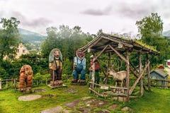 O norueguês cinzelou esculturas de madeira das pescas à corrica e uma rena em um fundo das montanhas na manhã enevoada Folklo esc imagem de stock