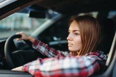 O novato fêmea do motorista olha fora da janela de carro fotos de stock royalty free