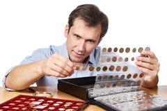 O numismata do homem examina sua coleção da moeda foto de stock