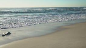 O oceano é profundamente azul, as ondas é lavado pelo Sandy Beach da costa do verão, os raios do sol filme