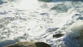 O oceano é profundamente azul, as ondas é lavado pelo Sandy Beach da costa do verão, os raios do sol video estoque