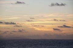 O Oceano Atlântico extensões Nubla-se o céu azul Um jogo da luz solar NASCER DE O SOL Fotografia de Stock