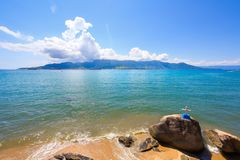 O oceano bonito, cruz fixou a uma pedra fotografia de stock royalty free