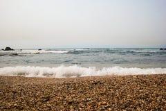 O oceano em Porto com seixos e espuma Foto de Stock Royalty Free