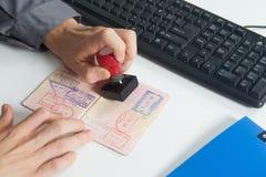O oficial carimbará no passaporte Fotografia de Stock