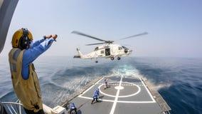 O oficial da plataforma de helicóptero dá o sinal de mão ao helicóptero do falcão do mar de Sikorsky S-70 que paira acima da plat imagens de stock royalty free