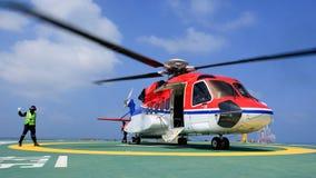 O oficial de aterrissagem de helicóptero dá o sinal ao passageiro a embar Fotografia de Stock